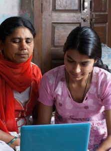Rural Indian Women Using Laptop with Her Daughter in the Room.