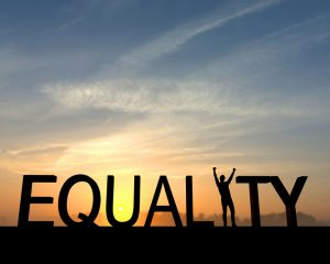 The word equality is silhouetted against an orange and blue sunset. The I in the word is made from a figure with their arms raised up in the air in a successful victory pose.